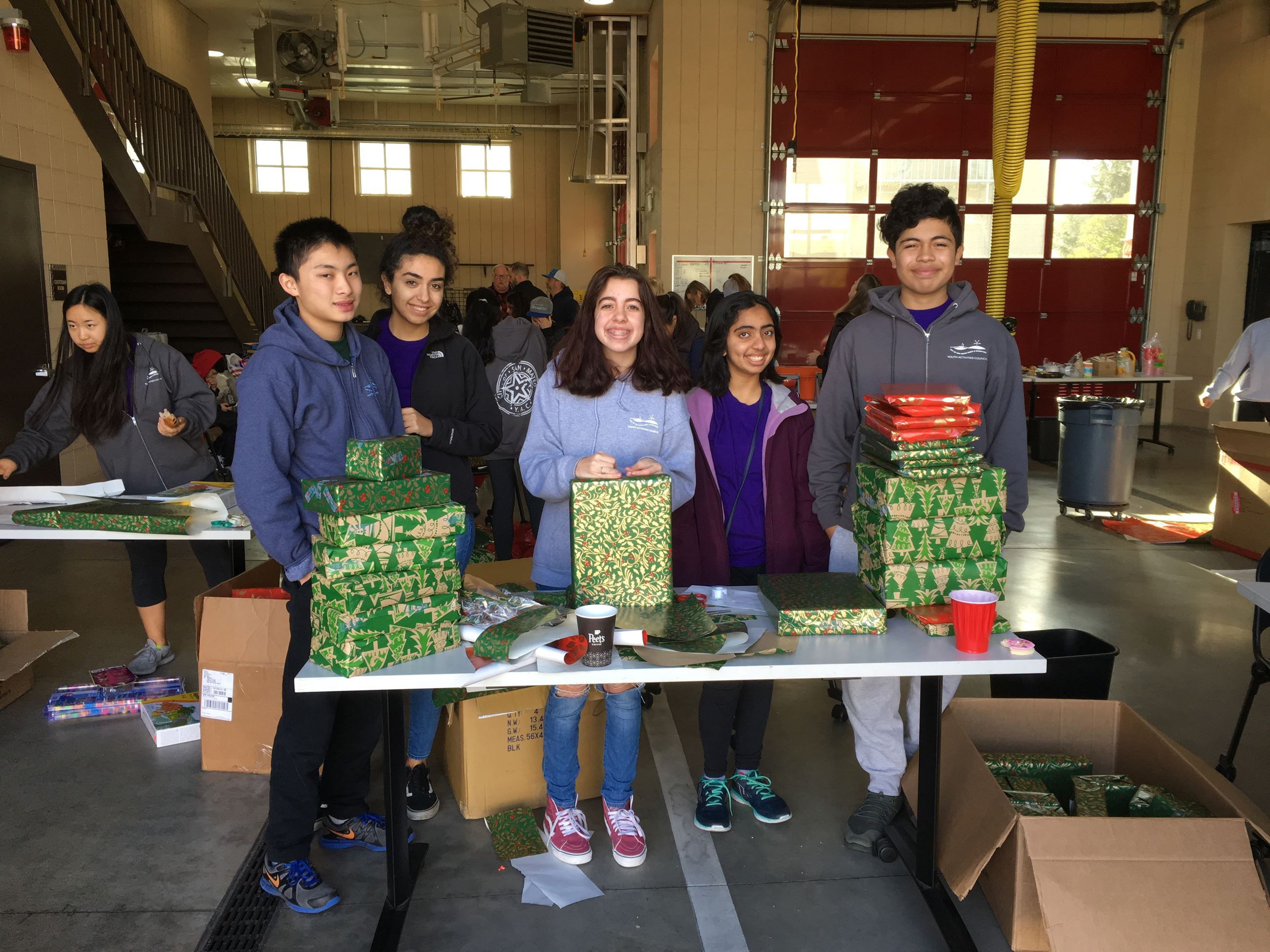 Photo of YAC members wrapping gifts for Toys for Tots at Fire Station 23.